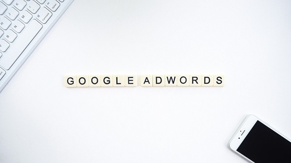 Google AdWords spelled with Scrabble tiles on a white surface.