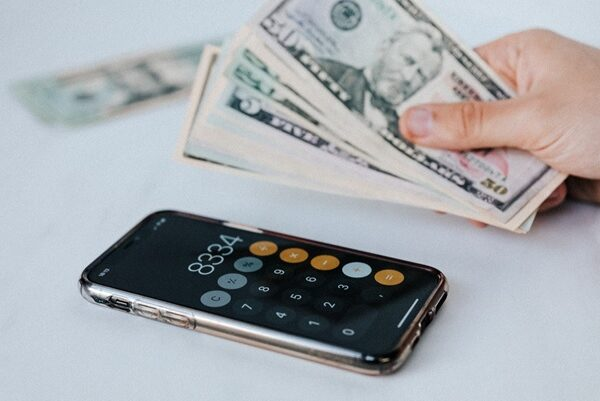 A person holding cash in their hand next to an iPhone with the calculator app open