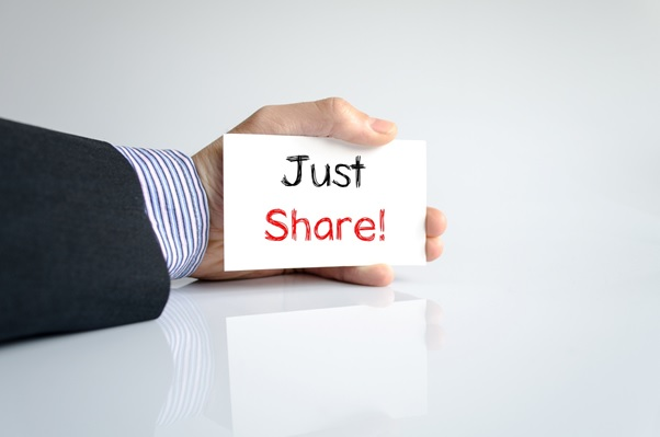 a man holding a card saying just share